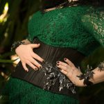 Melian, dark forest nymph, with a leafy green lace gown, black silk corset and black and silver leaves, crystals and horns.
